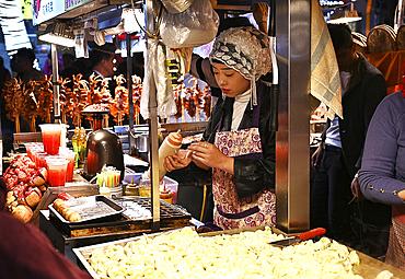 Muslim woman selling food at stall in Huajue night market, Xian, Shaanxi, China, Asia