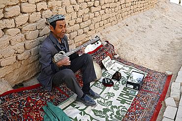 Uyghur man playing a Rawap, traditional Uyghur lute, in Gaochang, ruined Silk Road city, Xinjiang, China, Asia