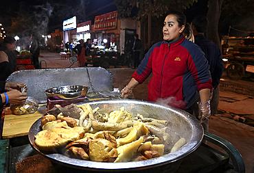 Woman selling cooked meats from rickshaw stall in Turfan night market, Turfan, Xinjiang, China, Asia