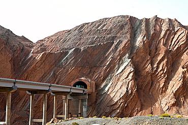 Recent Silk Road construction through solid rock in the Taklamakan Desert near Kuche, Xinjiang, China, Asia