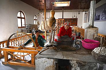 Uyghur women spinning silk thread from cocoons in traditional silk workshop, Jiya, Xinjiang, China, Asia