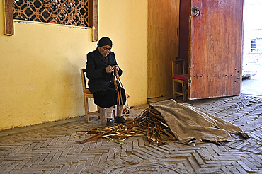 Uyghur woman stripping bark from Mulberry branches for paper making, Hotan, Xinjiang, China, Asia