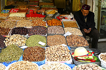 Uyghur Muslim stallholder selling locally grown and dried fruit and nuts, Kashgar, Xinjiang, China, Asia