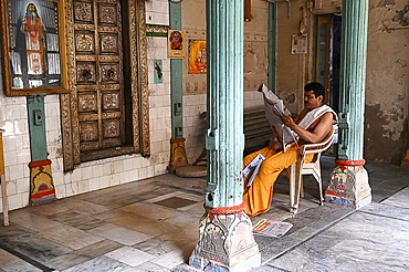 Hindu priest reading the daily newspaper at an old backstreet temple in the palls (alleyways) of old Ahmedabad, Gujarat, India, Asia