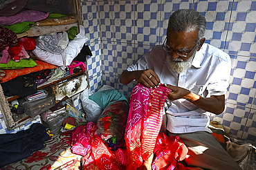 Tailor hand embroidering gold thread onto fabric in his tiny booth in the palls (alleyways) of old Ahmedabad, Gujarat, India, Asia