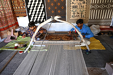 Two men weaving patterned wool carpet on a hand built traditional wooden loom, Bhuj, Gujarat, India, Asia