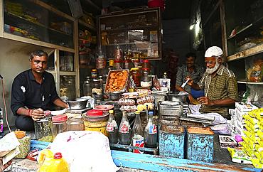 Village general stores, Muslim shopkeeper measuring honey for a customer, Dasada village, Gujarat, India, Asia