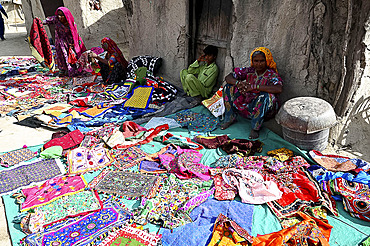 Women displaying their hand embroidered cloths, garments and bags in the desert village of Jarawadi, Kutch, Gujarat, India, Asia
