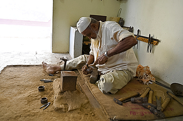 Muslim bell maker beating copper into shape to make bells by hand for cattle or for the home, Nirona village, Gujarat, India, Asia