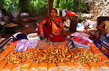 Adivasi woman selling freshly cooked pakora at traditional village fair celebrating Holi festival, Gujarat, India, Asia