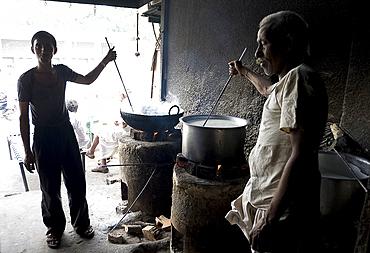 Young man and blind man stirring milk for chai, roadside chai stall, Dangiyawas, Rajasthan, India, Asia