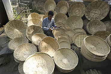 Basketmaker reading newspaper whilst waiting for customers in early morning market on the banks of the Brahmaputra river, Guwahati, Assam, India, Asia