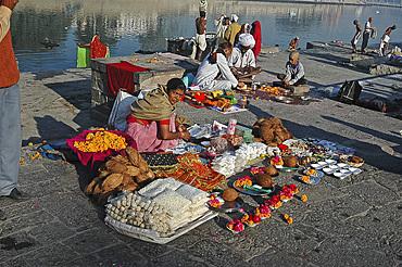 Woman selling holy puja items at sunrise by the sacred Shipra river, Ujjain, Madhya Pradesh, India, Asia