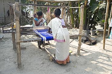 Two women weaving at household loom, Ganeshpahar village, Brahmaputra, Assam, India, Asia