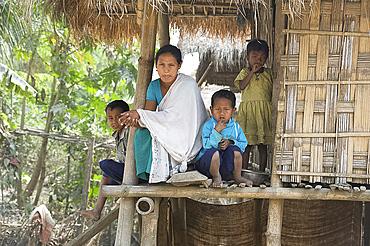 Mishing tribal family on the verandah of their family home, Majuli Island, Assam, India, Asia