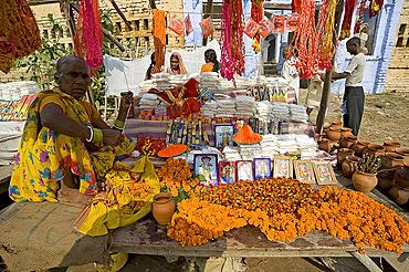 Woman selling marigold mala (garlands), pictures of Hindu deities, agarbathi (joss sticks) and rolimoli temple threads from stall at Sonepur Cattle Fair, near Patna, Bihar, India, Asia