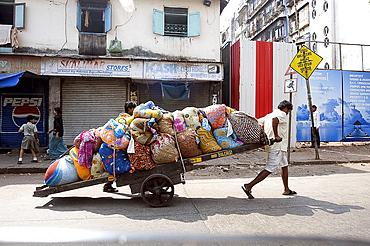 Laundrymen (dhobi wallahs), pulling wooden cart laden laundry from hotels for washing at Mahalaxmi dhobi ghats, Mumbai, India, Asia