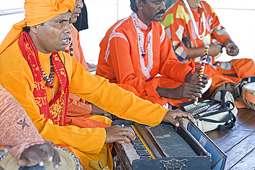 Hindu musicians singing ragas and playing ten scale Indian harmonium keyboard, tabla, pipe and hand cymbals, West Bengal, India, Asia