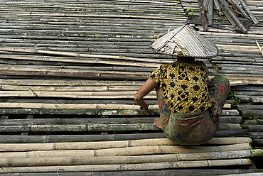Iban tribeswoman mending bamboo longhouse verandah floor, Lemanak River, Sarawak, Malaysian Borneo, Malaysia, Southeast Asia, Asia