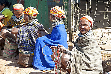 Bonda tribeswomen in traditional dress with beaded caps and metal necklaces selling beads at weekly market, Rayagader, Orissa, India, Asia