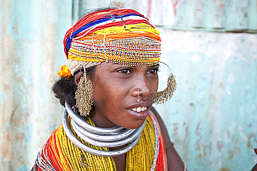 Bonda tribeswoman wearing traditional bead costume with beaded cap, large earrings, nose ring and metal necklaces at weekly market, Rayagader, Orissa, India, Asia