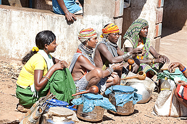Bonda tribeswomen wearing traditional beaded caps and metal necklaces, selling village-made alcohol at weekly market, Rayagader, Orissa, India, Asia