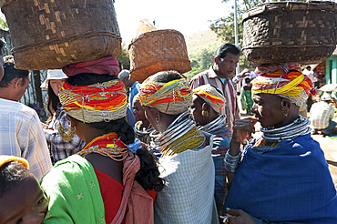 Bonda tribeswomen wearing traditional beaded caps and metal necklaces, with baskets on their heads at weekly market, Rayagader, Orissa, India, Asia