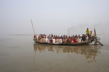 Ferry boat crossing the River Ganges in the early morning, carrying villagers and a bike strapped to the stern, Sonepur, Bihar, India, Asia
