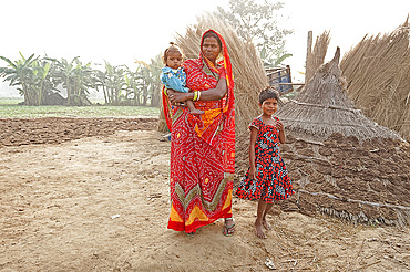 Mother in red sari and her two children in rural Bihari village at dawn, Sonepur, Bihar, India, Asia