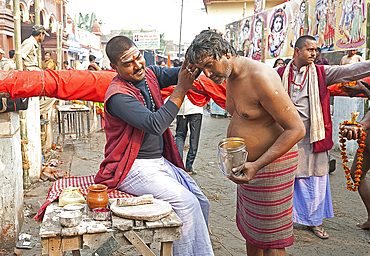 Pundit making Brahman sandalwood paste tilak on Hindu worshipper's forehead outside Hariharnath temple, Sonepur, Bihar, India, Asia