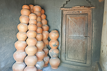 Potter's house porch, wooden front door and piles of clay pots stacked against the wall, near Rayagada, Orissa, India, Asia