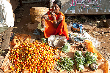 Woman at roadside vegetable stall selling tomatoes, beans and cauliflowers, rural Orissa, India, Asia