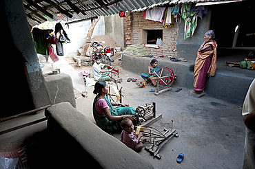 Women in communal back yard of weaving village, spinning silk thread ready for the looms, Vaidyanathpur weaving village, Orissa, India, Asia
