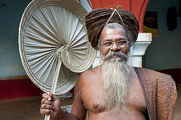 Joranda monk wearing tree bark cloth, holding palm leaf fan, with uncut hair piled up on top of his head, Joranda, Orissa, India, Asia