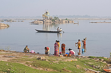 Women performing early morning ablutions in the River Mahanadi, men in fishing boat passing by, Vaidyanathpur, Orissa, India, Asia