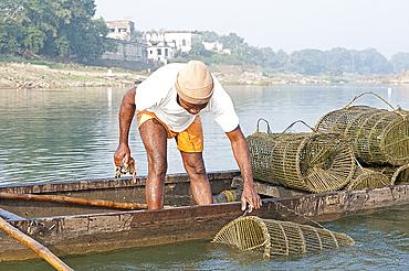 Fisherman in wooden boat, checking his fishing pots made from coir and bamboo, River Mahanadi, Orissa, India, Asia