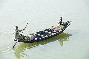 Village men punting a wooden boat along the River Hugli (River Hooghly), carrying bundles of alfalfa to market, near Kolkata, West Bengal, India, Asia