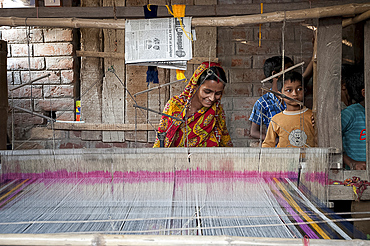 Village woman working on domestic loom with her children looking on, rural West Bengal, India, Asia