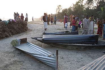 Villagers surrounding small boats made from single sheets of corrugated iron, lying on the banks of the River Hugli (River Hooghly), West Bengal, India, Asia