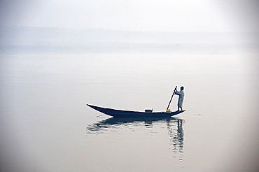 Man punting wooden boat along River Hugli (River Hooghly) at dawn, West Bengal, India, Asia