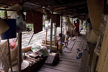 Iban tribal villagers sheltering from the rain on their longhouse verandah, Lemanak River, Sarawak, Malaysian Borneo, Malaysia, Southeast Asia, Asia