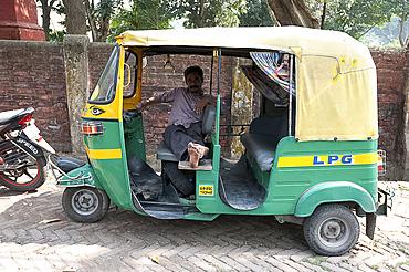 Rickshaw wallah waiting for custom in his rickshaw (tuk tuk), Barrackpore, West Bengal, India, Asia