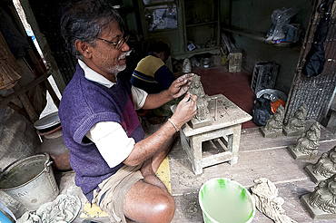 Master sculptor making models from clay from the River Hugli, to be painted for festival ceremonies, Kumartuli district, Kolkata, West Bengal, India, Asia