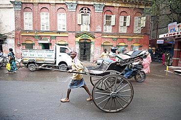 Running rickshaw wallah outside beautiful old Raj era Kolkata building in Kolkata backstreet, West Bengal, India, Asia