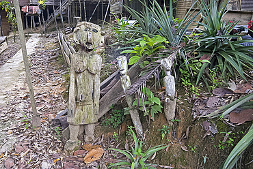 Carved spirits of men and a woman standing at the entrance to Iban tribal longhouse at Ngemah beach on the Lemanak River, Sarawak, Malaysian Borneo, Malaysia, Southeast Asia, Asia