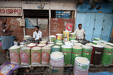 Rice wallahs sitting behind full sacks of rice waiting for customers in the early morning, New Market, Kolkata, West Bengal, India, Asia