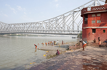 Men performing ablutions on ghats beneath the Howrah Bridge in the early morning, Kolkata (Calcutta), West Bengal, India, Asia