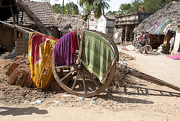 Washing drying over wooden cart wheel of wooden handcart in the street, Naupatana weaving village, rural Orissa, India, Asia