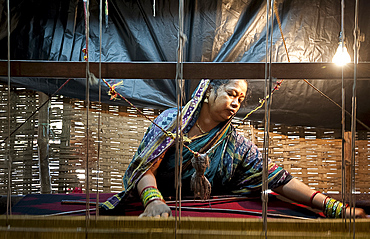 Woman in blue patterned sari weaving at loom in rough village shack, Naupatana weaving village, rural Orissa, India, Asia