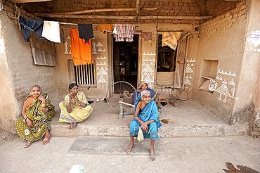 Women sitting chatting on verandah, painted with traditional Orissa patterns in rice flour, Naupatana weaving village, Orissa, India, Asia